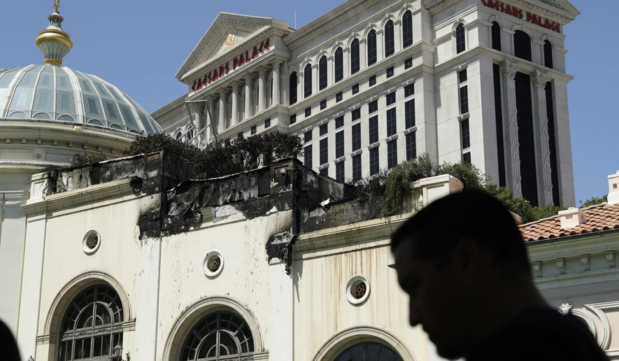 People look at fire damage at the Bellagio casino and resort, Friday, April 14, 2017, in Las Vegas. A fire official says a late Thursday blaze damaged decorative facing on the roof of a shopping and restaurant annex at the resort on the Las Vegas Strip. (AP Photo/John Locher)