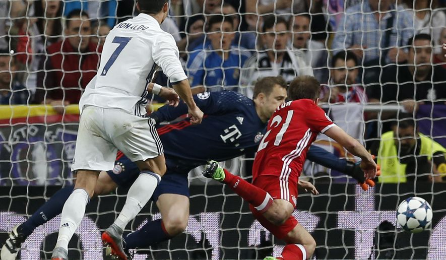 Real Madrid's Cristiano Ronaldo, left, scores his side's first goal passing Bayern goalkeeper Manuel Neuer, center right, during the Champions League quarterfinal second leg soccer match between Real Madrid and Bayern Munich at Santiago Bernabeu stadium in Madrid, Spain, Tuesday April 18, 2017. (AP Photo/Francisco Seco)