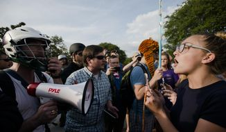 Kimberly Costen, Auburn freshman, right, yells at supports for Richard Spencer right to speak at Auburn University on Tuesday, April 18, 2017, in Auburn, Ala. The man who rented Foy Hall for Richard Spencer and was denied, filed a  law suit and was granted an injunction by a federal judge to allow Spencer to speak. (Albert Cesare/The Montgomery Advertiser via AP)