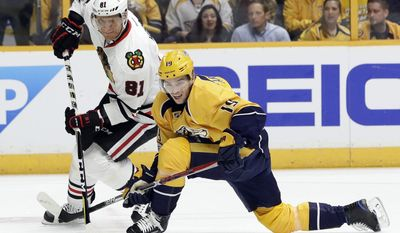 Chicago Blackhawks right wing Marian Hossa (81), of Slovakia, passes the puck past Nashville Predators center Calle Jarnkrok (19), of Sweden, during the first period in Game 3 of a first-round NHL hockey playoff series, Monday, April 17, 2017, in Nashville, Tenn. (AP Photo/Mark Humphrey)