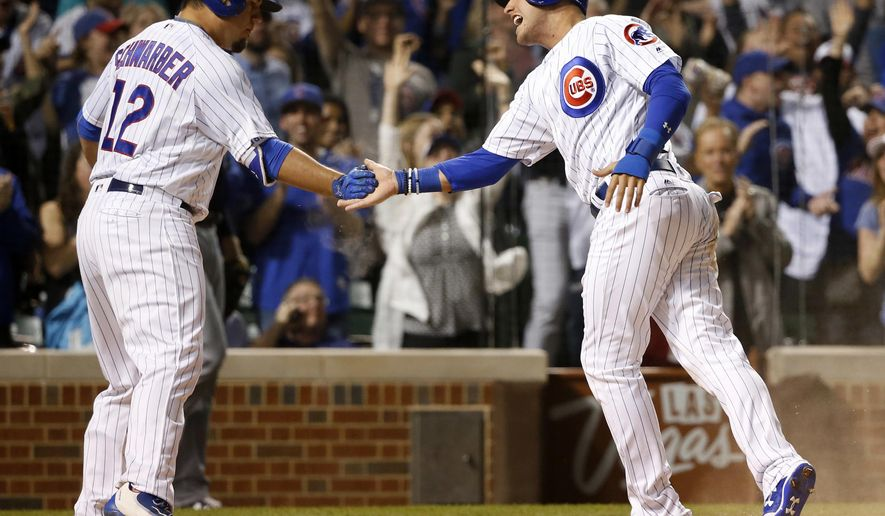Chicago Cubs' Kyle Schwarber (12) greets Albert Almora Jr. at home after Almora Jr. scored on a triple by Jon Jay, during the sixth inning of a baseball game against the Milwaukee Brewers on Tuesday, April 18, 2017, in Chicago. (AP Photo/Charles Rex Arbogast)