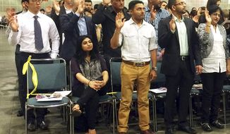 Indian-born U.S. national cricket team player Timil Kaushik Patel, center, takes an oath as a naturalized U.S. citizen at a ceremony in Los Angeles, Tuesday, April 18, 2017. His wife Pooja Patel is seated, left. Patel says becoming an American will help bring new players onto the team since there's only three spots allowed for non-citizen residents. (AP Photo/Amy Taxin)