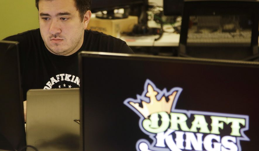 In this Sept. 9, 2015, file photo Len Don Diego, marketing manager for content at DraftKings, a daily fantasy sports company, works at his station at the company's offices in Boston. On June 19, 2017, the FTC put a pending merger of DraftKings and rival FanDuel on hold, citing antitrust concerns. (AP Photo/Stephan Savoia, File)