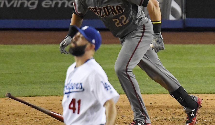Arizona Diamondbacks' Jake Lamb, right, hits a solo home run as Los Angeles Dodgers relief pitcher Chris Hatcher watches during the eighth inning of a baseball game, Monday, April 17, 2017, in Los Angeles. (AP Photo/Mark J. Terrill)