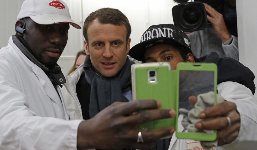 French presidential candidate Emmanuel Macron, center, poses for selfie with employees as he visits the meat paviIion at the Rungis wholesale food market, south of Paris, Tuesday April 18, 2017. Macron, an independent centrist with pro-business, pro-European views, is among the front-runners in France's unpredictable presidential race. The top two vote-getters in the first round Sunday will advance to the May 7 presidential runoff. (Philippe Wojazer; Pool via AP)