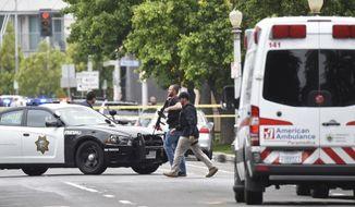 Fresno police members walk near a shooting scene Tuesday, April 18, 2017, in Fresno, Calif.  (John Walker/Fresno Bee/via AP)