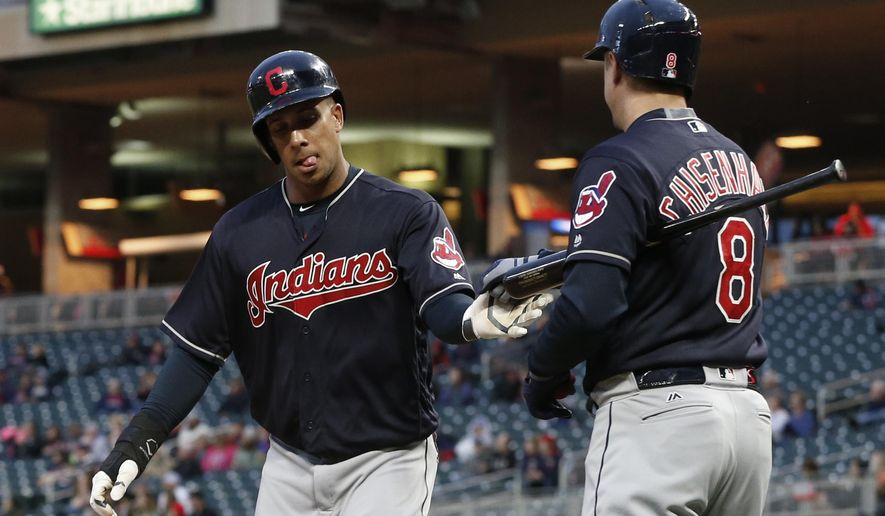 Cleveland Indians' Michael Brantley, left, is congratulated by Lonnie Chisenhall after scoring against the Minnesota Twins during the first inning of a baseball game Tuesday, April 18, 2017, in Minneapolis. (AP Photo/Jim Mone)