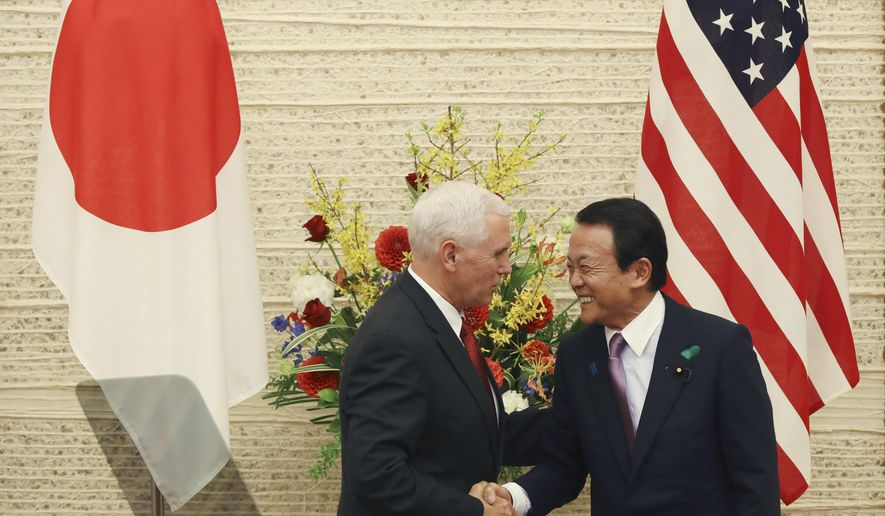 """U.S. Vice President Mike Pence, left, and Japanese Deputy Prime Minister and Finance Minister Taro Aso shake hands as they end the joint press conference at the prime minister's office in Tokyo, Tuesday, April 18, 2017. After meeting with Japanese Prime Minister Shinzo Abe, Pence held talks with Aso on a new U.S.-Japan """"economic dialogue"""" to be led by the two. The new forum for trade talks was launched by U.S. President Donald Trump and Abe during the Japanese leader's visit to the U.S. in February. (AP Photo/Eugene Hoshiko)"""