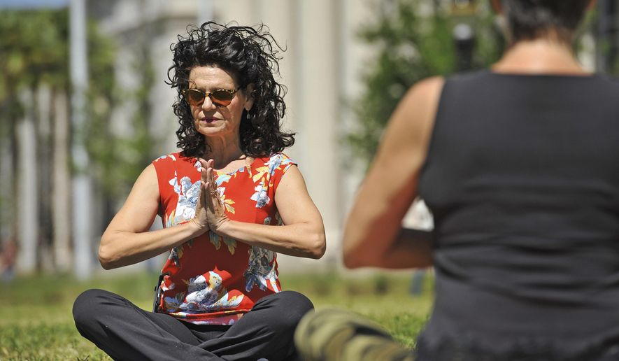 In this April 7, 2017. photo, County Court Judge Eleni Derke leads her yoga class on the lawn outside the Duval County Courthouse in Jacksonville, Fla. Derke is a certified yoga instructor. Derke holds her Yoga on the Lawn class once a month until the weather gets too hot. (Bob Self/The Florida Times-Union via AP)