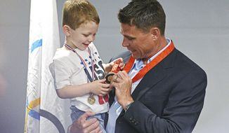 Derek Miles, University of South Dakota alum and current USD pole vaulting coach, holds his son Ariston, 3, after a presentation of an Olympic bronze medal by the International Olympic Committee, Monday, April 17, 2017, at the University of South Dakota in Vermillion, S.D. Miles placed fourth in the 2008 Olympics in Beijing, but the International Olympic Committee recently disqualified Denys Yurchenko, the third-place finisher, after retested samples showed Yurchenko used a banned substance. (Joe Ahlquist/The Argus Leader via AP)