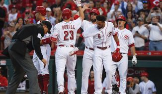 Cincinnati Reds' Adam Duvall (23) celebrates with Joey Votto, left, Jose Peraza, center right, and Billy Hamilton (6) after hitting a grand slam off Baltimore Orioles starting pitcher Kevin Gausman in the second inning of a baseball game, Tuesday, April 18, 2017, in Cincinnati. (AP Photo/John Minchillo)