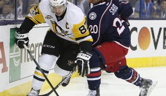 Pittsburgh Penguins' Sidney Crosby, left, controls the puck as Columbus Blue Jackets' Brandon Saad defends during the first period of Game 4 of an NHL first-round hockey playoff series Tuesday, April 18, 2017, in Columbus, Ohio. (AP Photo/Jay LaPrete)
