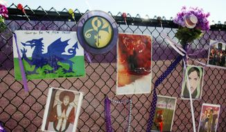 In this April 6, 2017, photo, fan artwork of Prince hangs on a new memorial fence in the parking lot of Paisley Park Museum, the former home and recording complex of the late superstar in Chanhassen, Minn. Affidavits and search warrants were unsealed in Carver County District Court Monday, April 17, 2017, as the yearlong investigation into Prince's death continues. (AP Photo/Jeff Baenen)