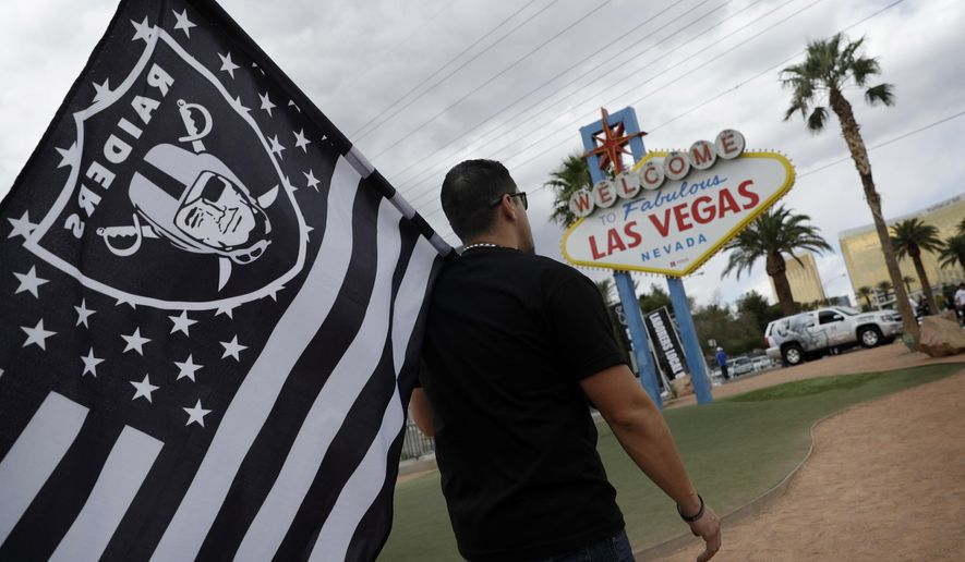 FILE - In this March 27, 2017, file photo, Matt Gutierrez carries a raiders flag by a sign welcoming visitors to Las Vegas, in Las Vegas. Taxpayers contributed over $4.6 million for an NFL stadium in Las Vegas during March, when an increase on area hotel taxes went into effect to cover the state's share of the project. (AP Photo/John Locher, File)