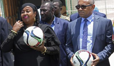 In this Monday April 17, 2017 photo, Confederation of African Football President Ahmad Ahmad, right, and Somali Sports Minister Khadija Mohamed Dirie, left, poses for a photo during a tour to a soccer stadium in Mogadishu, Somalia. Ahmad arrived in the Somali capital on Monday in a historic visit by the highest-ranking soccer leader to the long-chaotic horn of African nation. (AP Photo/Farah Abdi Warsameh)