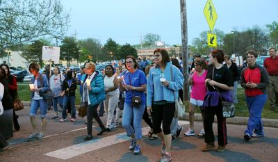 In a Monday, April 17, 2017 photo, more than 400 people march to the front of St. Francis Hospital in Topeka, Kan., in hopes of keeping the doors to St. Francis Hospital open. The owner of St.Francis, a nonprofit Catholic hospital in Topeka, said Tuesday that it will stop operating the facility this summer, whether or not it finds a buyer, and that Kansas' refusal to expand state health coverage for the needy contributed to the hospital's financial troubles.  (Keith Horinek/The Topeka Capital-Journal via AP)
