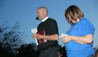 Pastor Jon Bruss of St. John's Lutheran Church gives the prayer along with Anna Munns, at the candle light vigil held at St. Francis Hospital in Topeka, Kan., on Monday, April 17, 2017, in hopes of keeping the doors to St. Francis Hospital open. The owner of St.Francis, a nonprofit Catholic hospital in Topeka, said Tuesday that it will stop operating the facility this summer, whether or not it finds a buyer, and that Kansas' refusal to expand state health coverage for the needy contributed to the hospital's financial troubles.  (Keith Horinek/The Topeka Capital-Journal via AP)