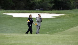 Investigators walk on a golf course as they examine debris that fell at the Breton Bay Golf and Country Club when an Army UH-60 helicopter from Fort Belvoir, Va., crashed, Monday, April 17, 2017, in Leonardtown, Md. (AP Photo/Alex Brandon)