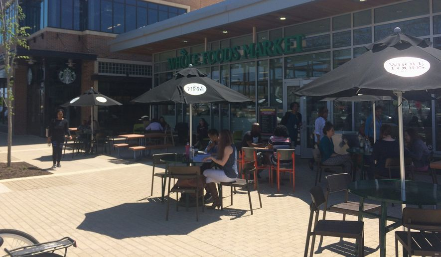 Customers dine at the Whole Foods market cafe in the new Riverdale Park Station shopping center. The store opened April 12 after six years fraught with delays. (Julia Brouillette/The Washington Times)