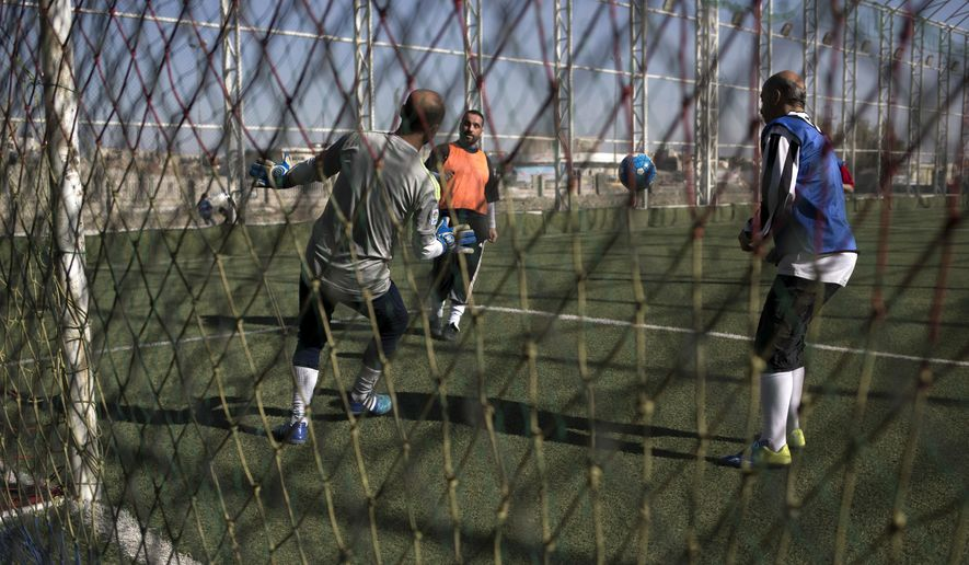 In this Wednesday, Feb. 8, 2017 photo, Mosul residents play soccer on a pitch in eastern Mosul. The soccer field was closed for four moths during fighting between the Islamic State group and Iraqi forces. (AP Photo/Bram Janssen)