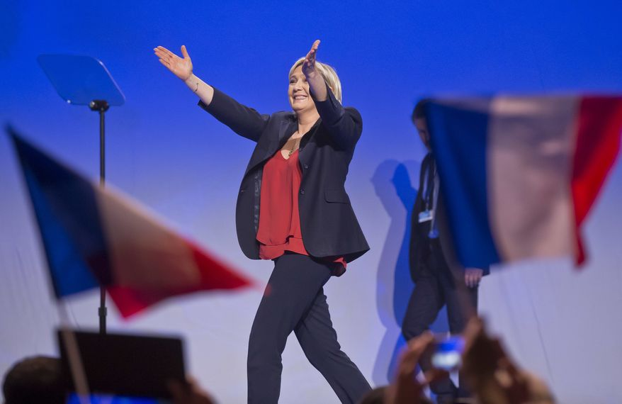Far-right leader and candidate for the 2017 French presidential election Marine Le Pen acknowledges applauses as she arrives on stage for a meeting in Marseille, southern France, Wednesday, April 19, 2017. Le Pen and centrist Emmanuel Macron are among four leading candidates seen as most likely to progress from Sunday's first round and to reach the May 7 runoff between the top two. (AP Photo/Michel Euler)