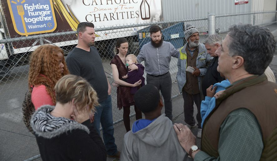 Community members and faith leaders from On Ramps Covenant Church hold a prayer and vigil in the alley behind the Catholic Charities' Fresno Family Resource Center to honor the three shooting victims that were killed by a gun man on Tuesday morning, April 18, 2017, in Fresno, Calif. Two of the victims were shot near the building by suspect Kori Ali Muhammad. (Silvia Flores/The Fresno Bee via AP)