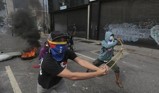 """Anti-government protesters launch stones with a sling during clashes in Caracas, Venezuela, Wednesday, April 19, 2017. Tens of thousands of opponents of President Nicolas Maduro flooded the streets of Caracas in what's been dubbed the """"mother of all marches"""" against the embattled socialist president. (AP Photo/Fernando Llano)"""