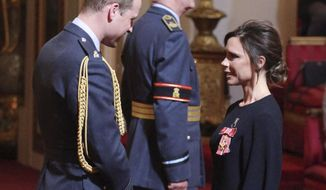 Fashion designer Victoria Beckham, right, receives her OBE from Britain's Prince William, the Duke of Cambridge during an investiture ceremony at Buckingham Palace in London, Wednesday April 19, 2017. (Yui Mok/PA via AP)