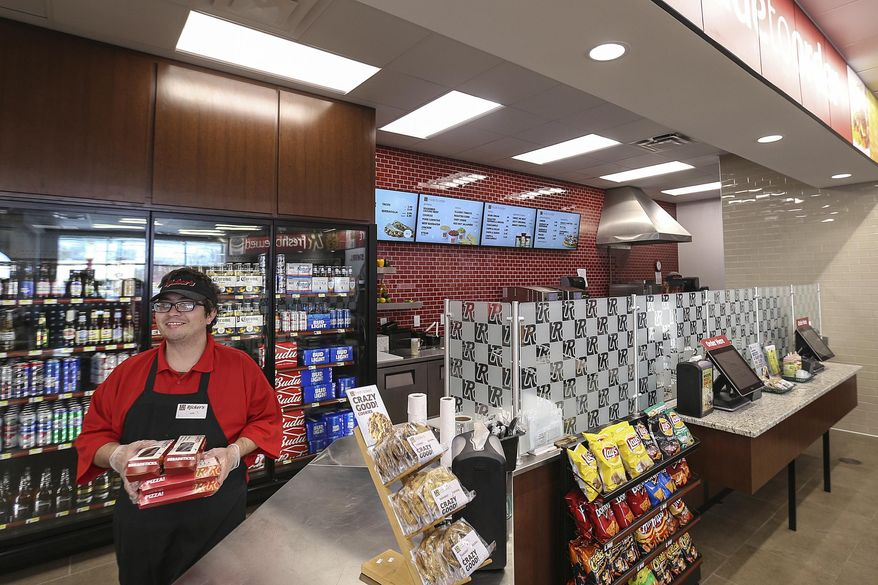 In this Thursday, March 23, 2017 photo, servers Kirk Adams prepares a food order behind the counter, where cold beer is kept in coolers at a Ricker's convenience store in Columbus, Ind. (Jenna Watson/The Indianapolis Star via AP)