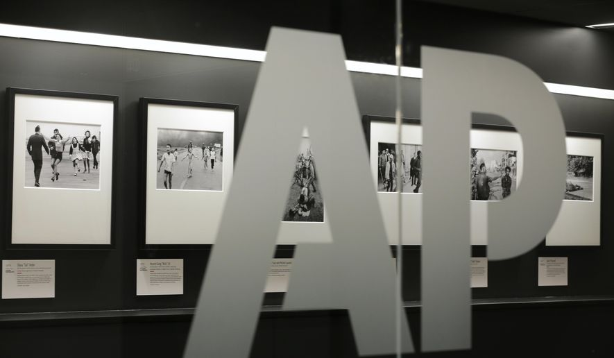 Associated Press photographs are displayed at the AP headquarters Tuesday, April 18, 2017, in New York. Earnings at the AP shrank substantially last year compared to 2015, when the news organization enjoyed a large tax benefit that skewed its results. The AP will hold its annual meeting in New York on Wednesday. (AP Photo/Jenny Kane)