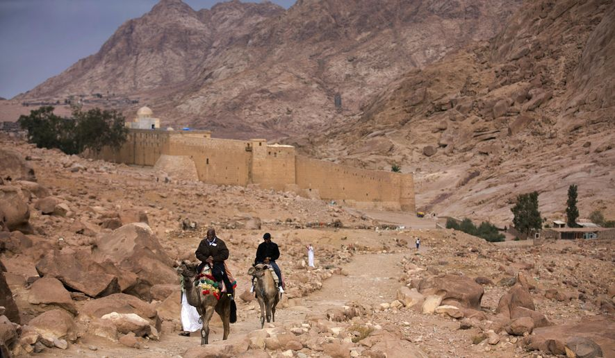 FILE -- In this Dec. 9, 2013 file photo, visitors leave Saint Catherine's Monastery on camels, in Saint Catherine, Egypt. The Islamic State extremist group said Tuesday, April 18, 2017, that its militants carried an attack on a police checkpoint near the famed Monastery in Sinai, which Egyptian security authorities said killed one policeman and wounded four. The attack on the monastery, built in the 6th century and a popular site for tourists visiting the Red Sea resorts along Sinai's southern coast, comes just over a week after suicide bombers attacked two churches in the Nile Delta city of Tanta and the coastal city of Alexandria, killing 45 people on Palm Sunday. (AP Photo/Hiro Komae, File)