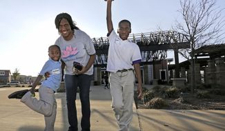 ADVANCE FOR PUBLICATION RELEASE MONDAY, APRIL 24, 2017, AT 12:01 A.M. CT AND THEREAFTER In this Feb. 10, 2017 photo, Chanelle Cook poses with her sons Matthew, left, and Emmitt, right, near their home in Buckeye Trail Commons development in Dallas. A single mother, Cook, 33, lives in the new and nice Buckeye Trail Commons, which is located in the relative isolation of South Dallas. (Louis DeLuca/The Dallas Morning News via AP)