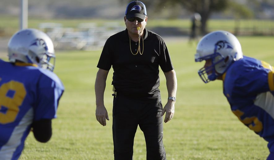 File - In this Oct. 22, 2014 file photo, Pahranagat Valley Panthers head coach Ken Higbee directs his team during practice in Alamo, Nev. Higbee, who has coached a rural Nevada high school eight-man football team that won 104 straight games and eight state championships, is being accused of stealing more than $120,000 in public funds. (AP Photo/John Locher, File)