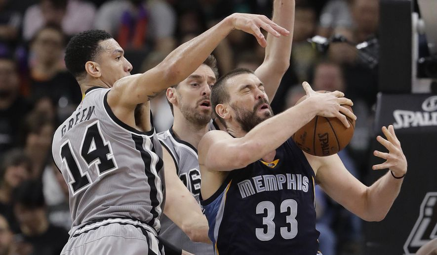 FILE - In this April 15, 2017, file photo, Memphis Grizzlies center Marc Gasol (33) is defended by San Antonio Spurs guard Danny Green (14) and center Pau Gasol during the second half in Game 1 of a first-round NBA basketball playoff series, in San Antonio. Pau and Marc Gasol have been battling each other on a basketball court since they were children with the older brother always finding ways to win. Now little brother Marc is doing his best to rally the Grizzlies to avoid being swept away in their first playoff meeting.  (AP Photo/Eric Gay, File)