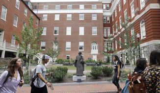 FILE - In this Sept. 1, 2016, file photo, students walk past a Jesuit statue in front of Freedom Hall, center, formerly named Mulledy Hall, on the Georgetown University campus, Thursday, Sept. 1, 2016, in Washington. Freedom Hall was renamed Isaac Hawkins Hall on April 19, 2017, in honor of the first person listed in documents related to an 1838 sale of slaves in order to pay off the school's debts. The school and the group of Catholic priests that founded it apologized for the sale. (AP Photo/Jacquelyn Martin, File)