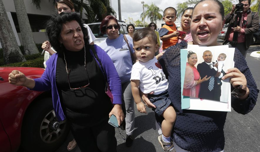 Elissett Saenz, right, walks with members of the immigrant community with her son Emanuel as she holds a photograph of her husband Charlie Rodriguez outside of the office of Congresswoman Ileana Ros-Lehtinen, Wednesday, April 19, 2017, in Miami. Rodriguez has been detained since he went to a scheduled appointment with ICE in March. Advocates and lawyers say these routine check-ins are increasingly resulting in the detention of immigrants who are in the country illegally but have no criminal record. (AP Photo/Lynne Sladky)