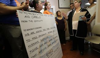 Immigrant rights groups present a petition asking lawmakers to help release a Nicaraguan asylum seeker, who was detained after a routine check-in with U.S. Immigration and Customs Enforcement in South Florida, at the office of Congresswoman Ileana Ros-Lehtinen, Wednesday, April 19, 2017, in Miami. At right is Ros-Lehtinen's Chief of Staff Maytee Sanz. Espilvio Sanchez-Benavidez is slated for deportation even as he continues to appeal his case in federal court. (AP Photo/Lynne Sladky)