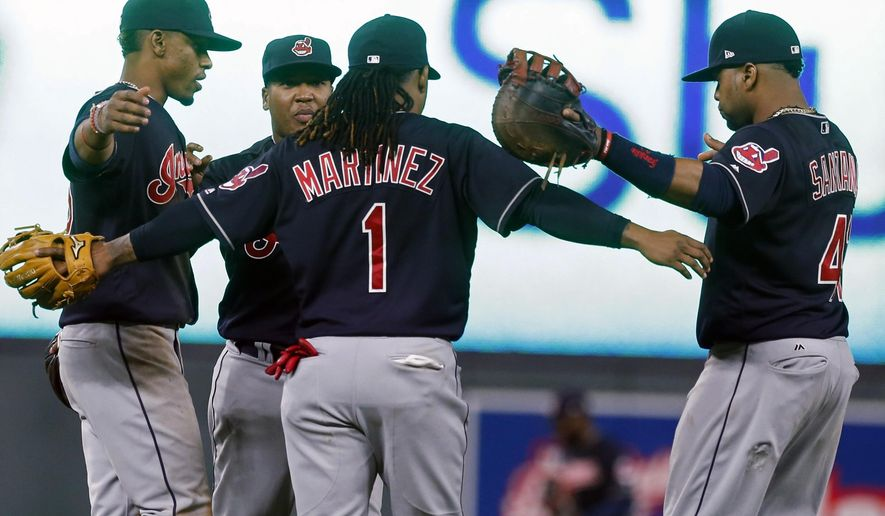 Cleveland Indians players celebrate the team's 11-4 win over the Minnesota Twins in a baseball game Tuesday, April 18, 2017, in Minneapolis. From left are Francisco Lindor, Jose Ramirez, Michael Martinez and Carlos Santana. (AP Photo/Jim Mone)