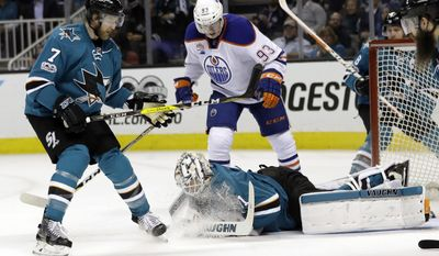 San Jose Sharks goalie Martin Jones, bottom, makes a stop next to teammate Paul Martin (7) and Edmonton Oilers' Ryan Nugent-Hopkins (93) during the second period in Game 4 of a first-round NHL hockey playoff series Tuesday, April 18, 2017, in San Jose, Calif. (AP Photo/Marcio Jose Sanchez)