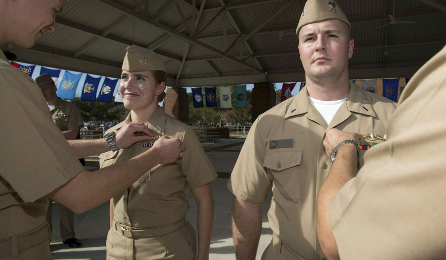 FILE - In this Dec. 5, 2012, file photo, released by the U.S. Navy, Lt j.g. Marquette Leveque, left, and Lt. j.g. Kyle McFadden, both of the USS Wyoming, receive their pins to indicate that they're qualified to serve on submarines in a ceremony at Naval Submarine Base Kings Bay in Georgia. With women now serving on submarines, future subs are being built to specifically accommodate gender differences including height, reach and strength. The first vessel built with some of the new features is expected to be delivered in 2021. (James Kimber/U.S. Navy via AP, File)