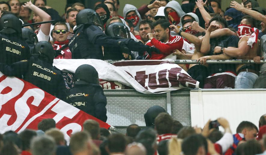 Spanish riot police scuffles with Bayern fans during the Champions League quarterfinal second leg soccer match between Real Madrid and Bayern Munich at Santiago Bernabeu stadium in Madrid, Spain, Tuesday April 18, 2017. (AP Photo/Francisco Seco)