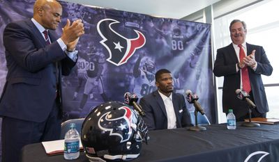 Houston Texans general manager Rick Smith, left, and Texans chief operating officer Cal McNair, right, give a standing ovation to former Texans wide receiver Andre Johnson during a retirement ceremony for Johnson at NRG Stadium on Wednesday, April 19, 2017, in Houston. Johnson signed a one-day contract to retire as a Texans player. ( Brett Coomer/Houston Chronicle via AP)