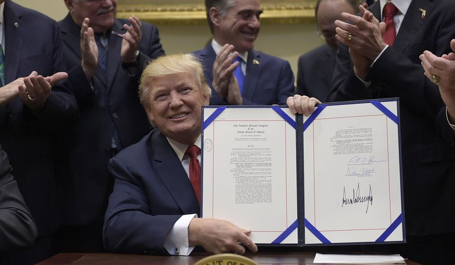 President Donald Trump hold up the Veterans Choice Program Extension and Improvement Act that he signed,  Wednesday, April 19, 2017, in the Roosevelt Room of the White House in Washington. (AP Photo/Susan Walsh)