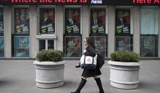 A woman walks past the News Corp. headquarters building displaying posters featuring Fox News Channel personalities including  Bill O'Reilly, top center, in New York, Wednesday, April 19, 2017. (AP Photo/Mary Altaffer)