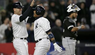 New York Yankees' Starlin Castro, center, celebrates his three-run homer with Matt Holliday during the fifth inning of the baseball game against the Chicago White Sox at Yankee Stadium, Wednesday, April 19, 2017, in New York. (AP Photo/Seth Wenig)