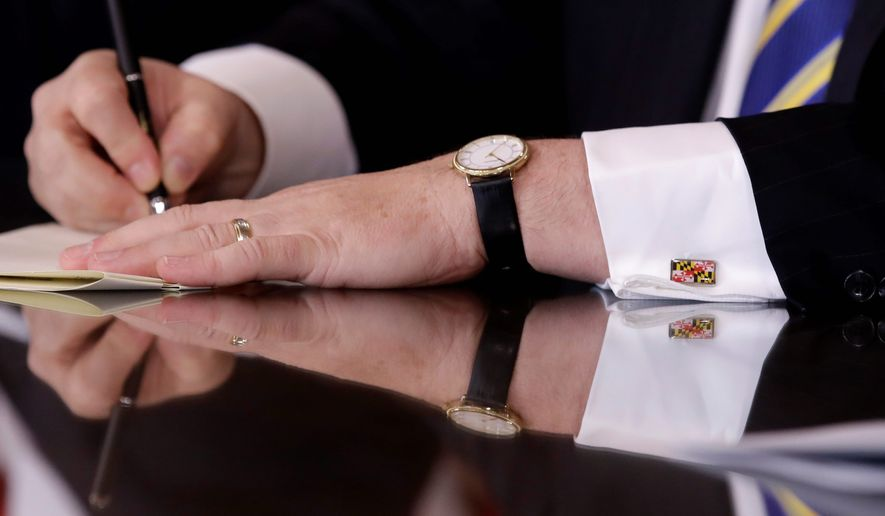Maryland Gov. Larry Hogan wears cufflinks depicting the Maryland state flag as he signs a bill during a bill signing ceremony following the state's legislative session at the Maryland State House in Annapolis, Md., Tuesday, April 11, 2017. (AP Photo/Patrick Semansky)