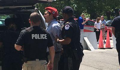 Police arrest DCMJ co-founder Adam Eidinger for distributing marijuana across the street from the U.S. Capitol on Thursday. (The Washington Times/Laura Kelly)