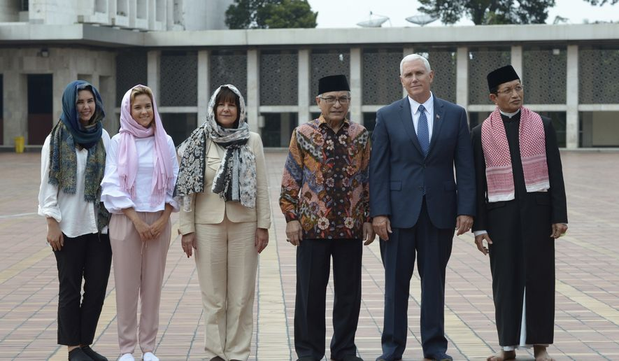 U.S. Vice President Mike Pence, second from right, pose for a photo with, from left to right, his daughters Audrey and Charlotte, his wife Karen, the Chairman of Istiqlal Mosque Muhammad Muzammil Basyuni and the Grand Imam of the mosque Nasaruddin Umar during his visit at the largest mosque in Southeast Asia, in Jakarta, Indonesia, Thursday, April 20, 2017. Pence praised Indonesia's democracy and moderate form of Islam after meeting Thursday with the president of the world's most populous Muslim nation. (Adek Berry/Pool Photo via AP)