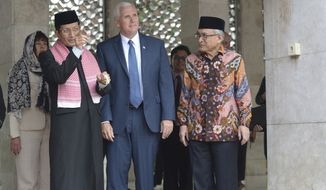 U.S. Vice President Mike Pence, center, is given a tour by the Grand Imam of Istiqlal Mosque Nasaruddin Umar, left, and the Chairman of the mosque Muhammad Muzammil Basyuni, right, during his visit to the largest mosque in Southeast Asia, in Jakarta, Indonesia, Thursday, April 20, 2017. Pence praised Indonesia's democracy and moderate form of Islam after meeting Thursday with the president of the world's most populous Muslim nation. (Adek Berry/Pool Photo via AP)