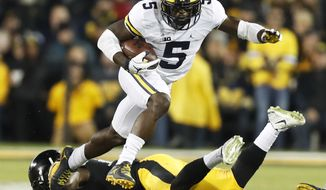 FILE - In this Nov. 12, 2016, file photo, Michigan's Jabrill Peppers (5) breaks a tackle by Iowa defensive back Desmond King, rear, during the first half of an NCAA college football game, in Iowa City, Iowa. Peppers is an explosive athlete who was mostly used as a linebacker in 2016, but does not have an obvious position fit. The versatility could get him into the second half of the first round, but the 'tweener' label could push him out. (AP Photo/Charlie Neibergall, File)